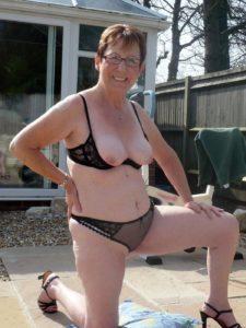 Mature amateur vrouw gaat naakt in de tuin